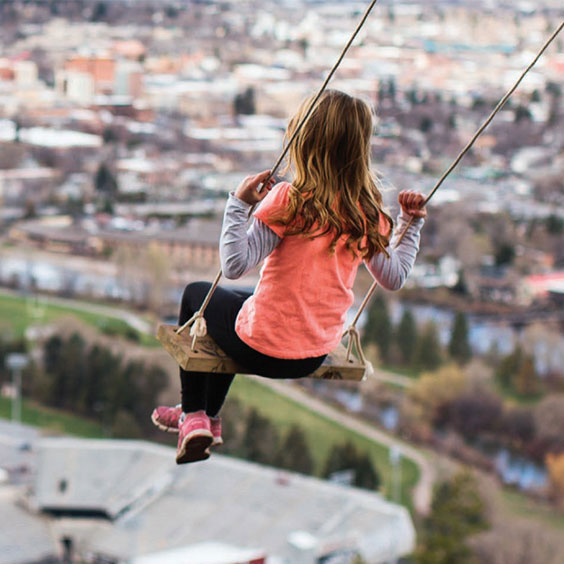 Young girl playing on a swing overlooking the Missoula valley.