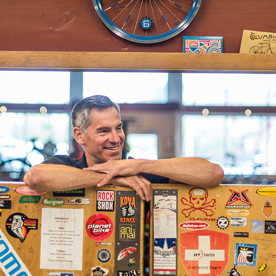 smiling man leaning on sticker bedecked wall within business