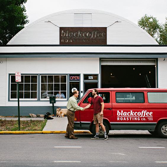 two men shaking hands in front of blackcoffee roasting co. van and building