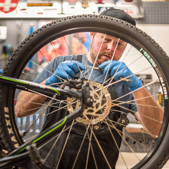 bicycle technician working on back tire and gears