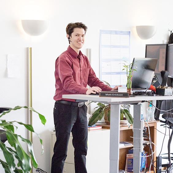 smiling man wearing headset at standing desk