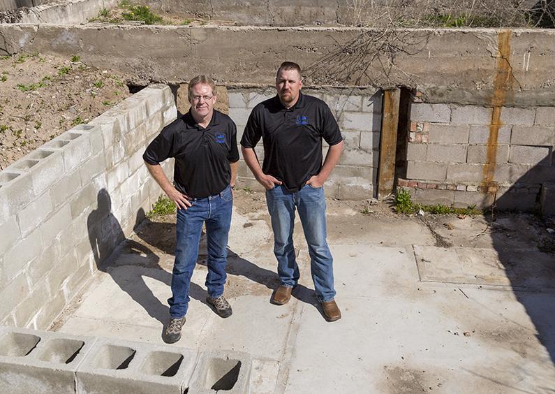Two men standing in deconstructed basement.