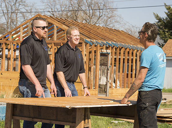 3 men standing outside around a table at a construction site.