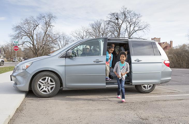 Young girl exits her families mini-van.