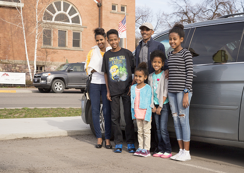 Family poses for a group photo along side their new mini-van.