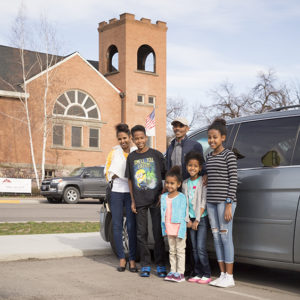 Family standing together by a mini van outside of a church.