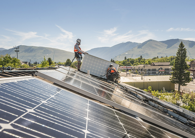 Workers installing solar panels with the M and L on the mountains in the background.