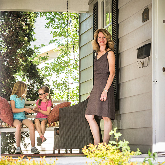 woman standing on porch while two girls sit on porch swing
