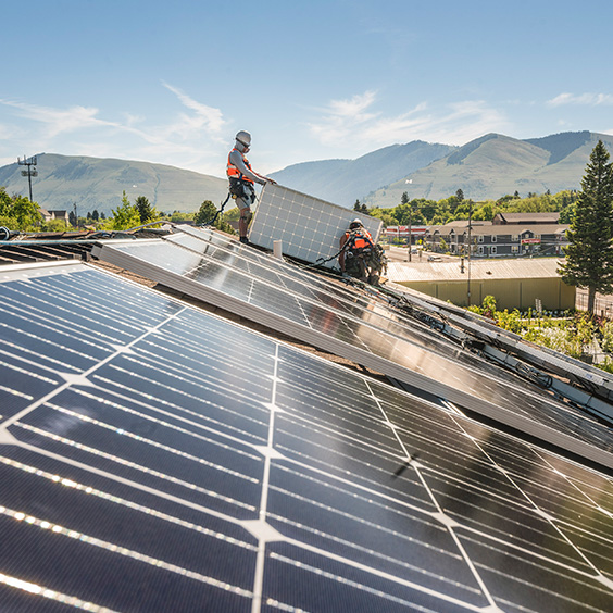 two workers adding photo voltaic panels to structure