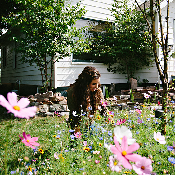 Smiling woman sitting in yard full of flowers.