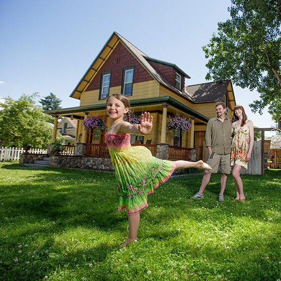 girl dancing in front yard of home with mom and dad