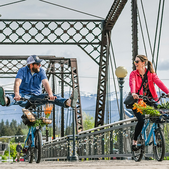 man and woman bicycling on steel bridge
