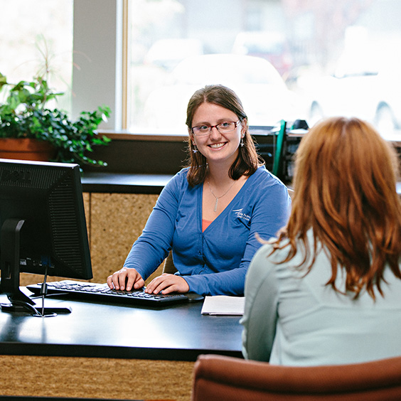 smiling woman at desk speaking to member