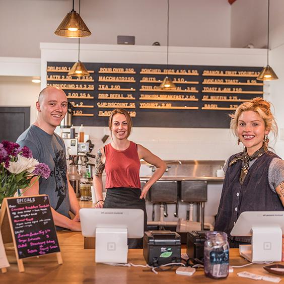 three smiling people around point of sale machine in restaurant