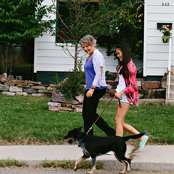 two women walking a dog in the neighborhood