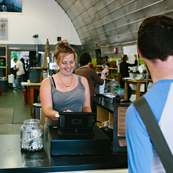 Smiling woman behind a cash register completing a sale.