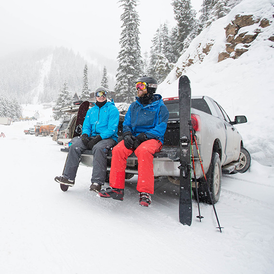 two skiers in the snow sitting on the tailgate of a truck