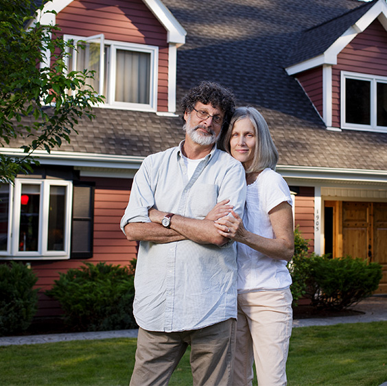 man and woman standing together in front of house