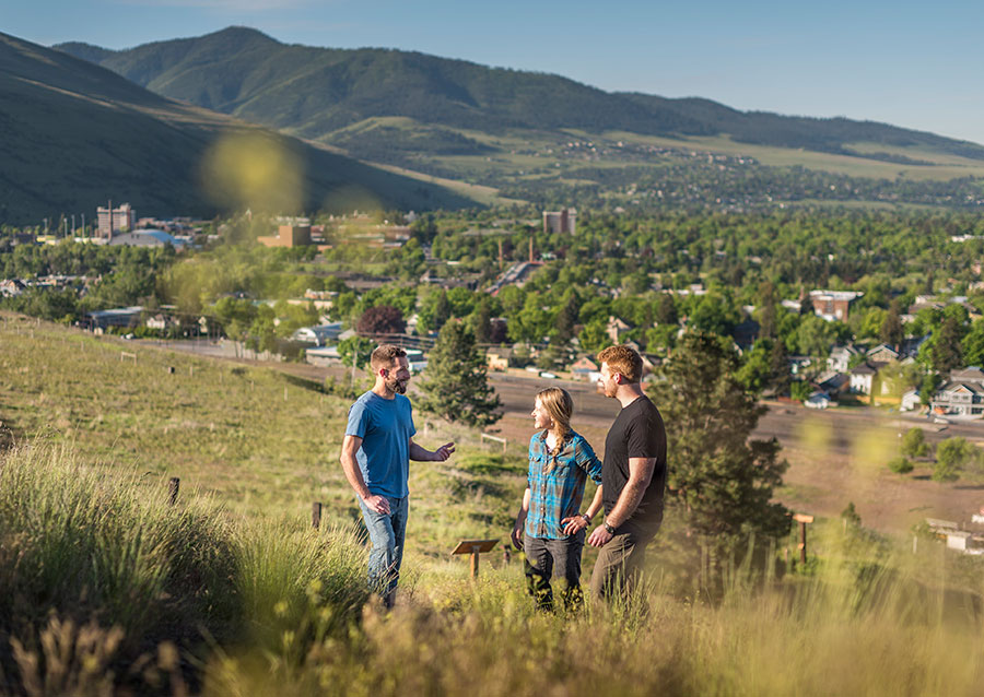 Two men and a woman standing on a hill talking with the Missoula valley in the background.
