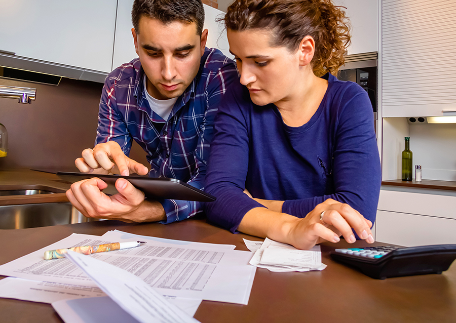Young couple reviewing their bank accounts with a digital tablet and calculator at home.