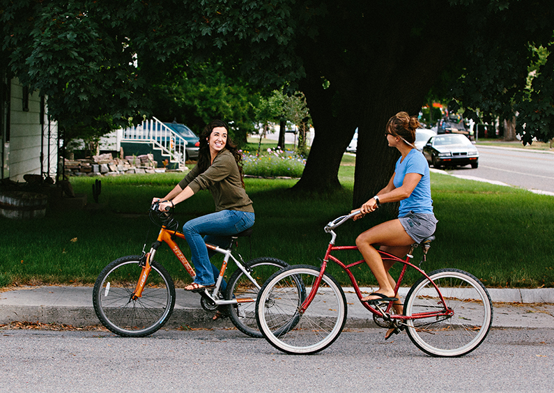 Two young women riding cruiser bikes down a residential street.