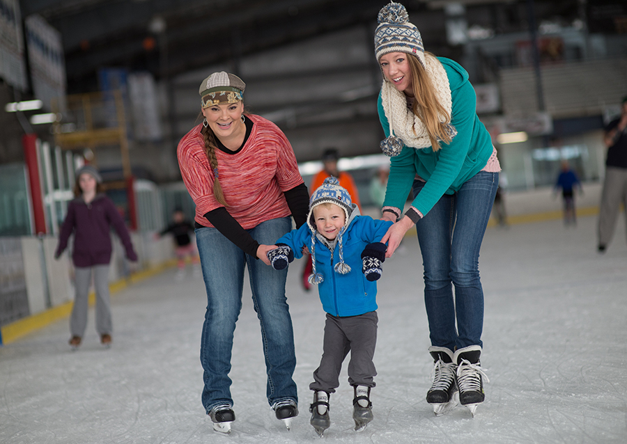 Two women helping a small boy learn to ice skate.