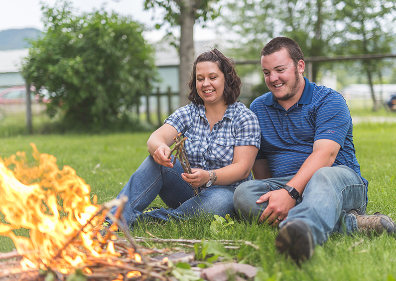 Man and woman sit in the backyard of their new house enjoying a camp fire.