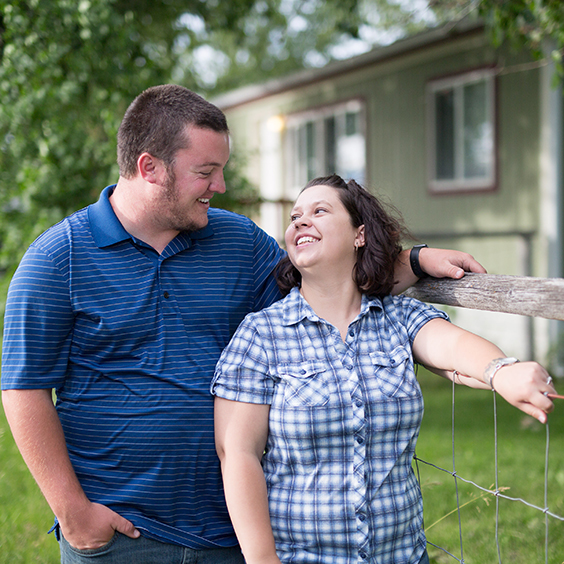 Young couple smiling at each other with a manufactured home in the background.