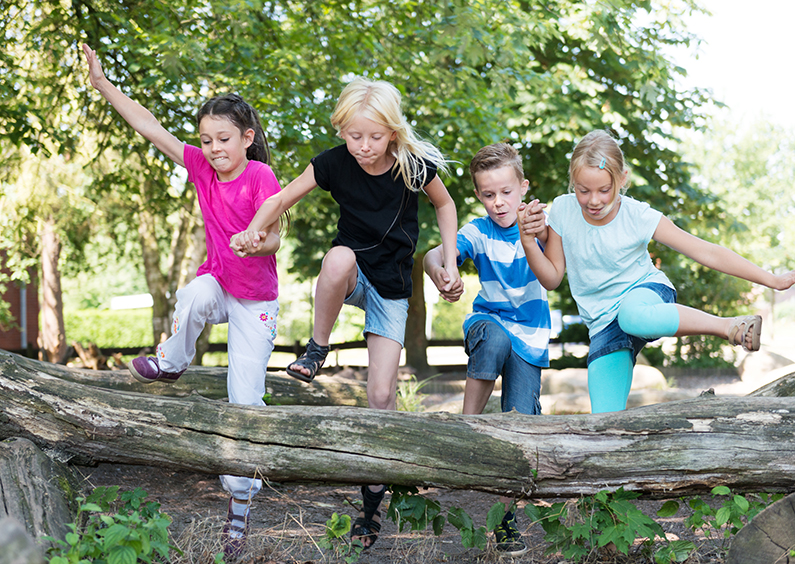 Four children jumping over a log outside.