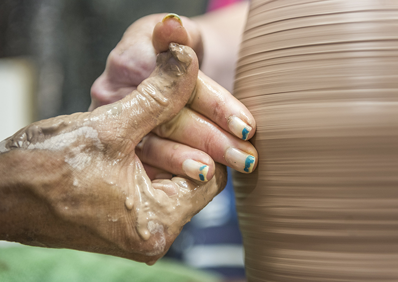 A ORI staffer guides the hand of a disabled person on clay on a pottery wheel.