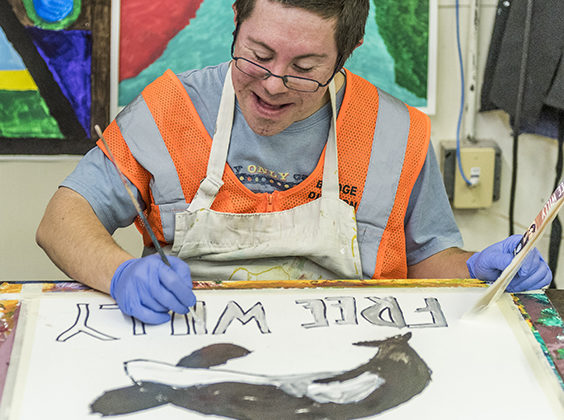 Young man smiling while painting a picture of Free Willy.