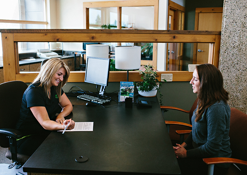 Two women sitting at desk with paperwork.