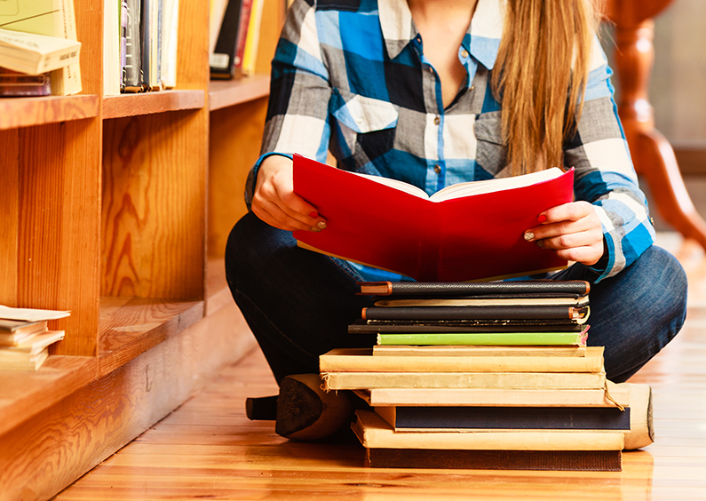 Education school concept. Female student sitting on floor in college library with a stack books reading.