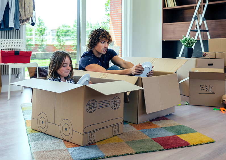 Young child and teenage boy playing in the living room in cardboard boxes made into cars.