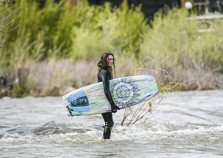 Young woman holding a river board on the Clark Fork River, Missoula MT.