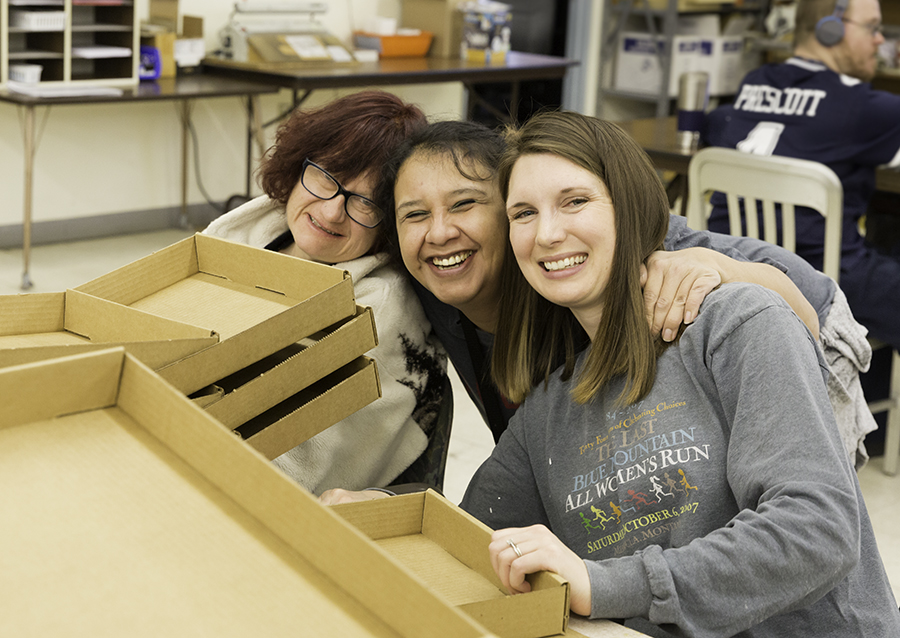 Three women leaning together smiling at the camera over a table with boxes being put together.