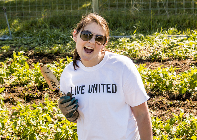 Employee holding a trowel in a Live United t-shirt.