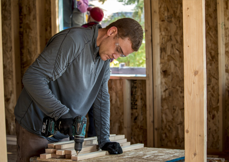 Man assembles pieces of wood with a hand held drill.
