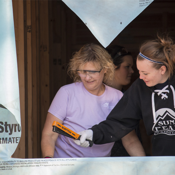 Two women are stapling a weather liner before installing a window.