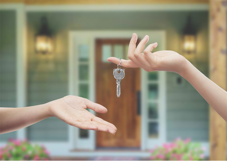 One hand is outstretched reaching for a set of keys in front of a new home.