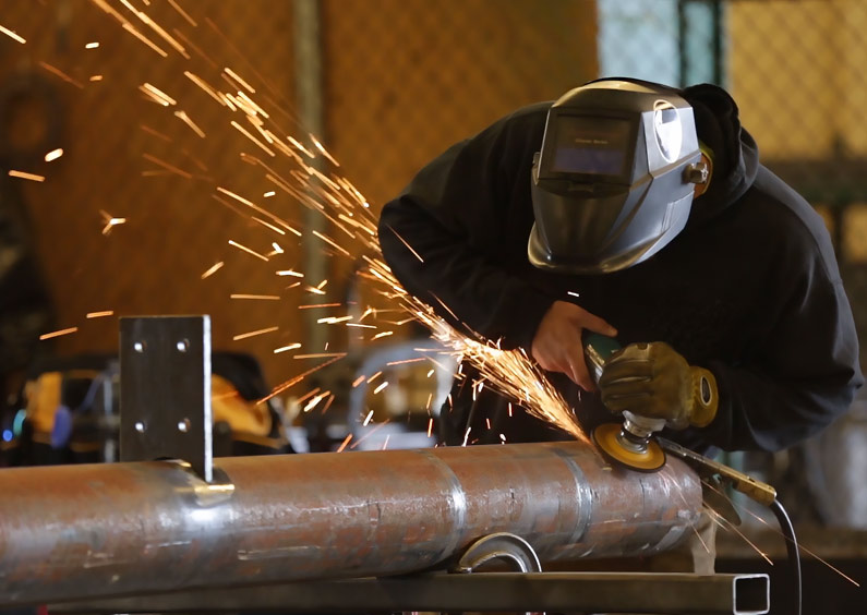A Welding student at the Missoula College working on a piece of the bus stop structure.