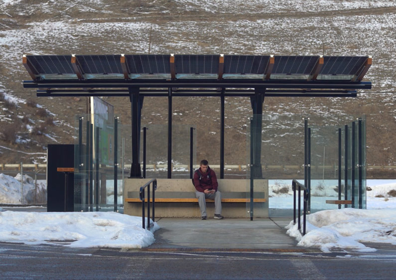 Photo of male Missoula College student sitting in a new bus stop shelter.