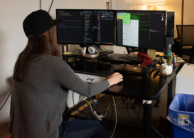 Student, Kathryn Kelly, working at a computer coding.
