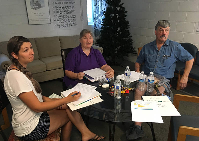 3 people sitting around a table discussing community options.