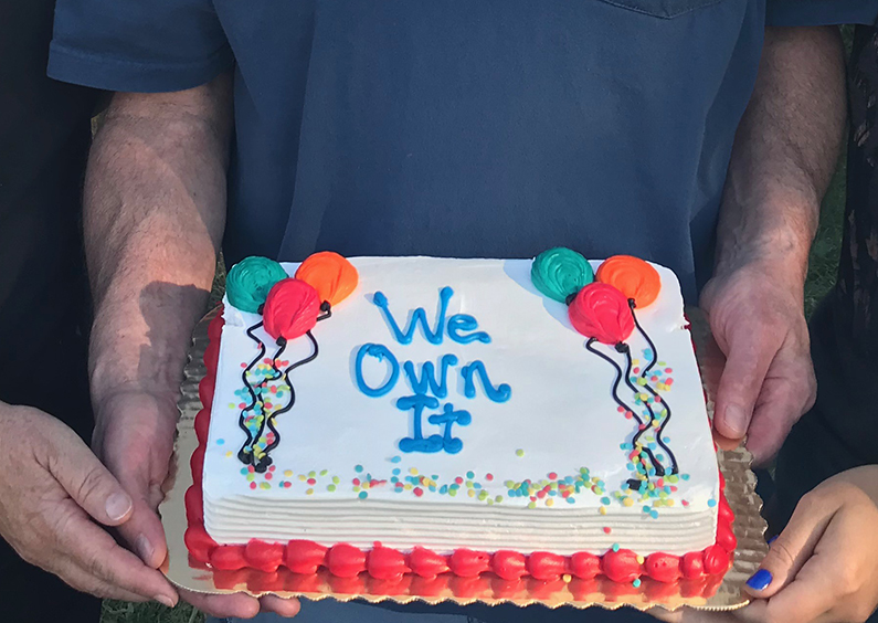 """3 sets of hands holding a cake that says """"We Own It""""."""